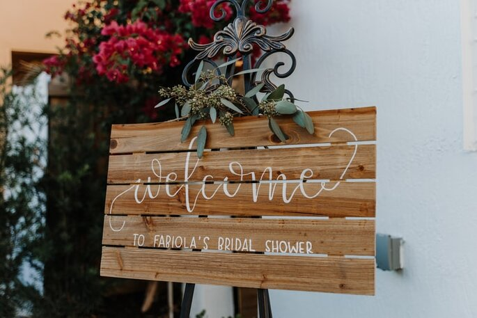 letrero para boda de madera con caligrafia cursiva y arreglos florales