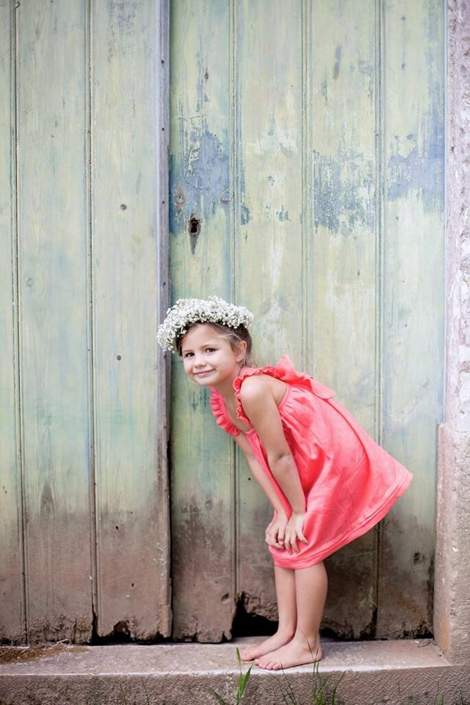 menina com vestido cor de rosas de alças e coroa de flores
