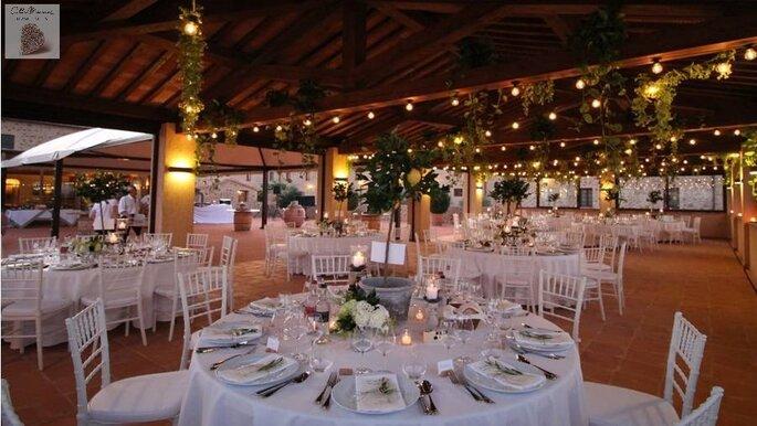 Dîner de mariage organisé en extérieur sous un préau, joliment illuminé à la tombée de la nuit