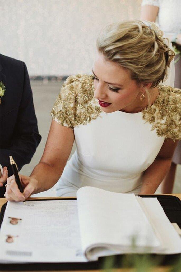 Braut unterschreibt Dokumente während der standesamtlichen Trauung