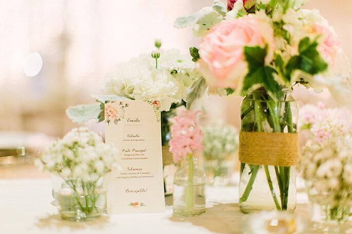 mesa de casamento com ementa design floral e flores rosa e branca com jarro de vidro e rafia