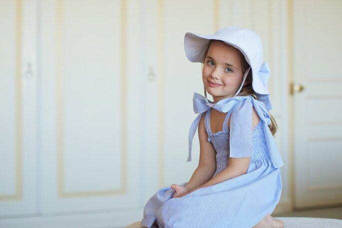 menina vestido azul de alças chapéu com um grande laço