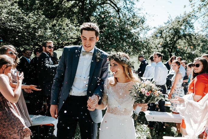 Ein Brautpaar im Blütenregen nach dem Ja-Wort.