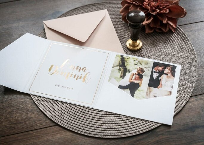 Quadratische Karte zum aufklappen. Rechts ist das Brautpaar zu sehen und links stehen in goldener Schrift ihre Namen und das Hochzeitsdatum.
