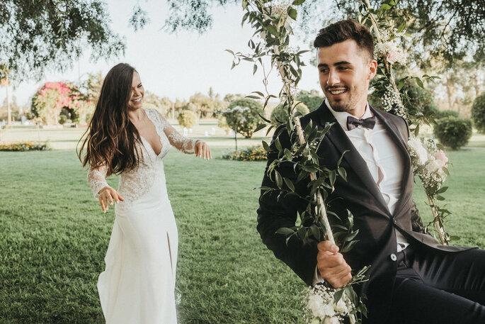 Noivos felizes, com o noivo num baloiço