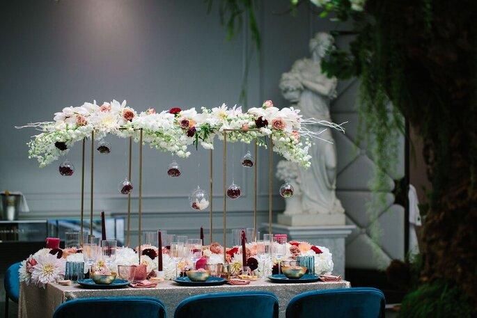 Une table décorée avec des fleurs, des guirlandes et des lampions à un mariage