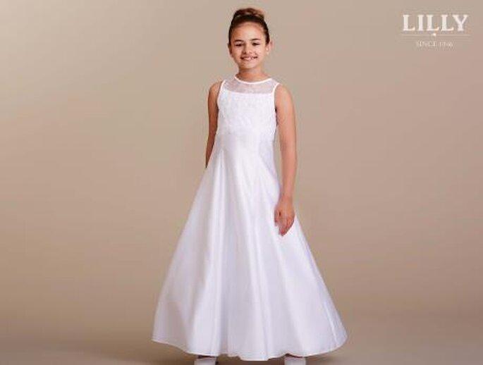 Ein Mädchen trägt ein weißes Kommunionskleid.