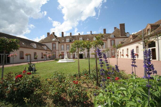 Un grand parc doté d'un jardin fleurit avec une fontaine blanche et un château en arrière-plan