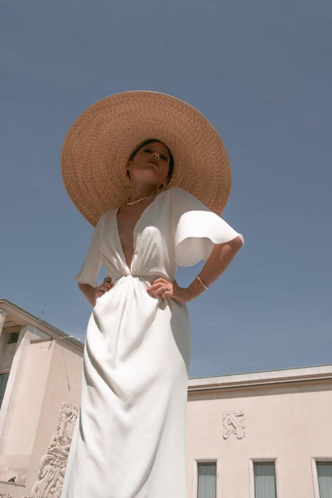Robe de mariée par Oksana Coquard - robe blanche avec un grand décolleté, dans une matière fluide et portée par un mannequin avec un chapeau de paille