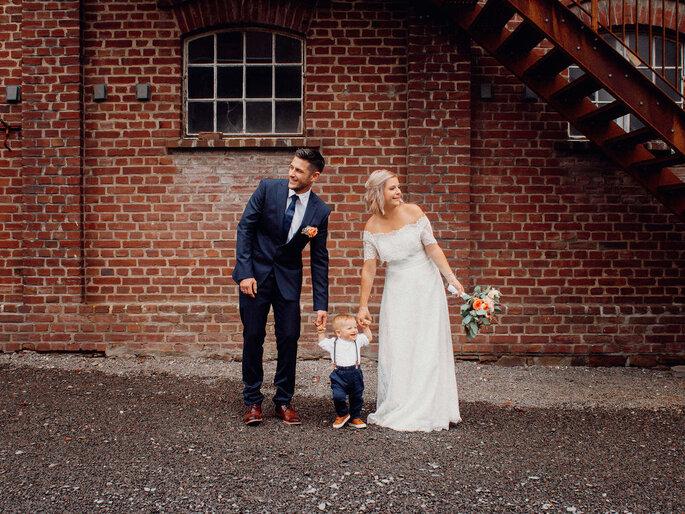 Ein Brautpaar mit Kleinkind vor einer Backsteinmauer.