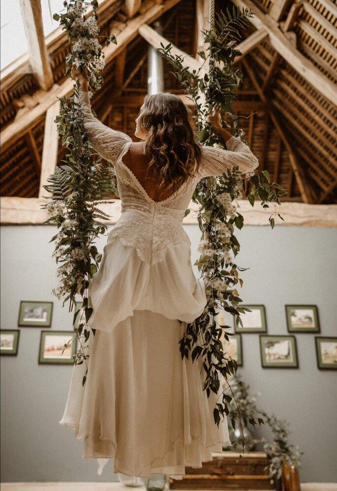 Une mariée sur une balançoire faite de lierre et de fleurs blanches