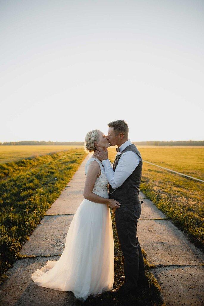 Hochzeitsfotos. Brautpaar küsst sich vor Sonnenuntergang