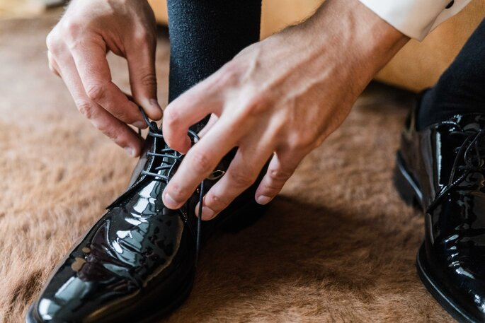 Getting Ready. Bräutigam zieht sich beim Getting Ready Schuhe an