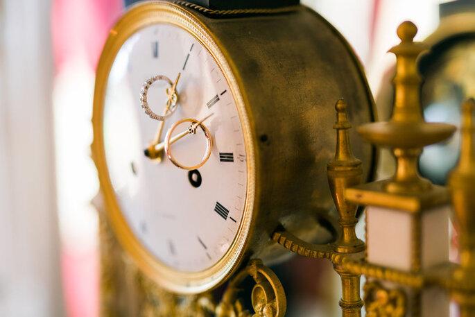 Les alliances des mariés prises en photo sur une horloge ancienne