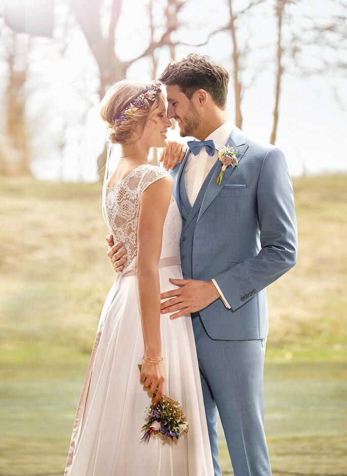 Eine Braut und ein Bräutigam auf einer grünen Wiese. Sie beide tragen Outfits von Haus der Braut in Mönchengladbach.