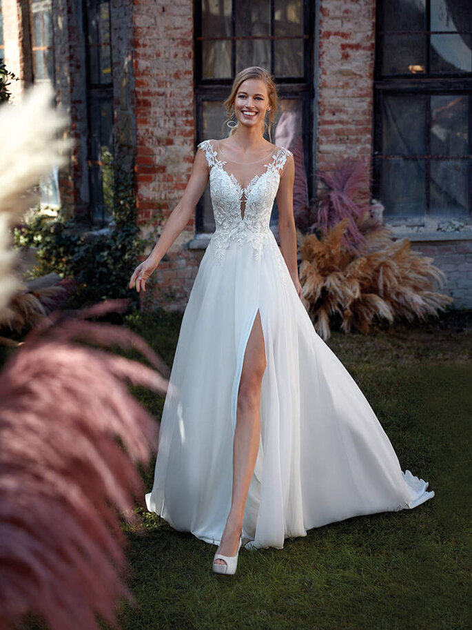 Robe de mariée ornée de jolies broderies florales au niveau du décolleté et fendue au niveau de la jupe.