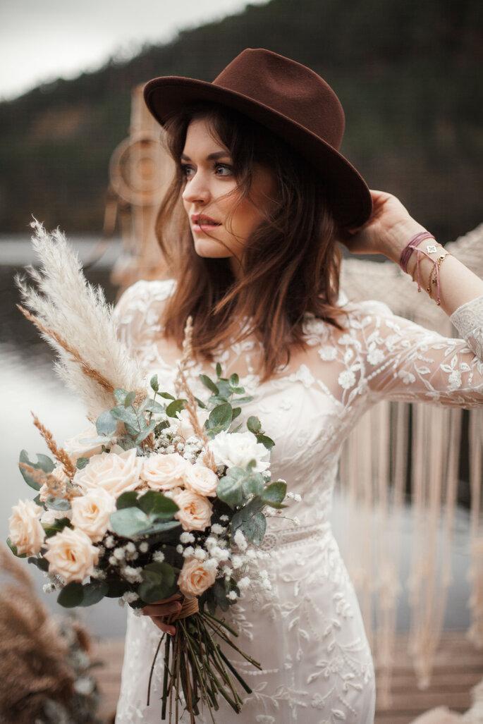 Eine Braut trägt ein Vintage-Brautkleid, einen opulenten Brautstrauß und einen braunen Hut.
