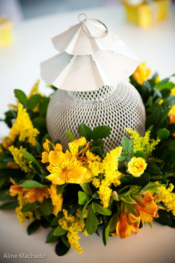 Centros de mesa hechos con faroles blancos y flores amarillas. Foto: Aline Machado