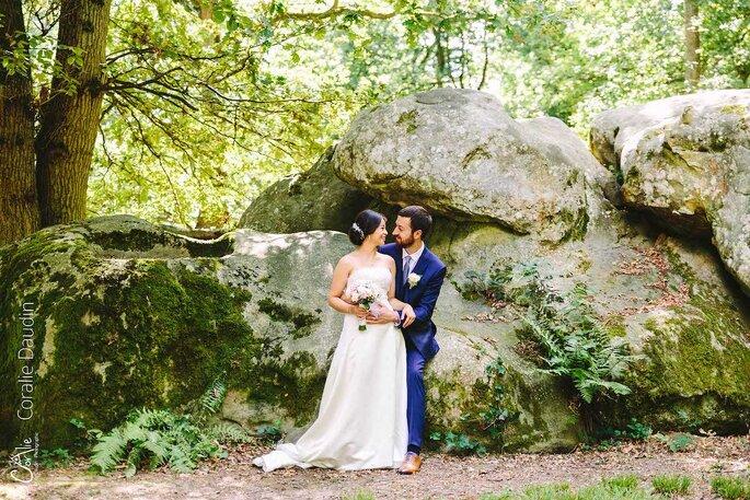 Un couple de mariés pose devant les roches du Manoir