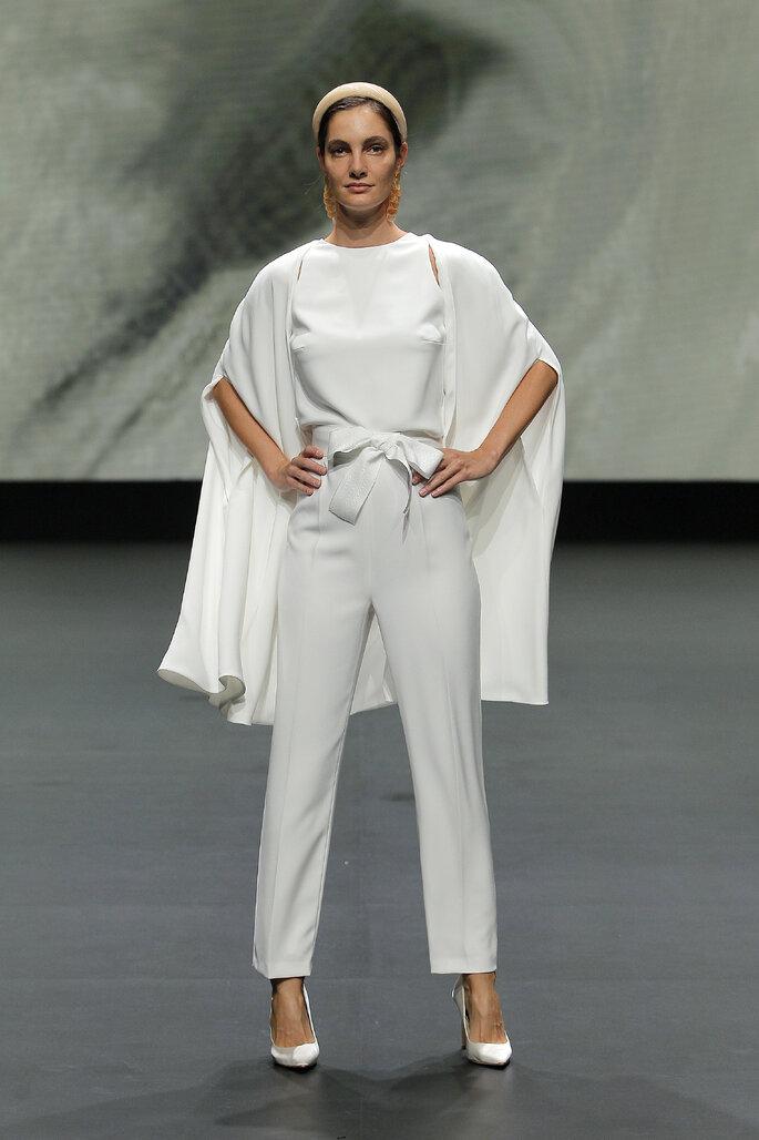 Colección Vestido de Novias 2021 Jesús Peiró vestido de novia alternativo con blusa de cuello redondo decorado con un lazo en la parte de abajo, con unos pantalones 3/4 y una capa larga