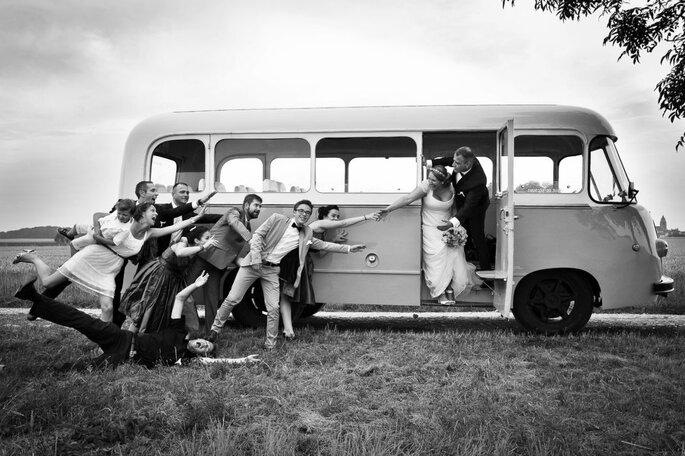 Un couple de mariés avec leurs invités devant un combi