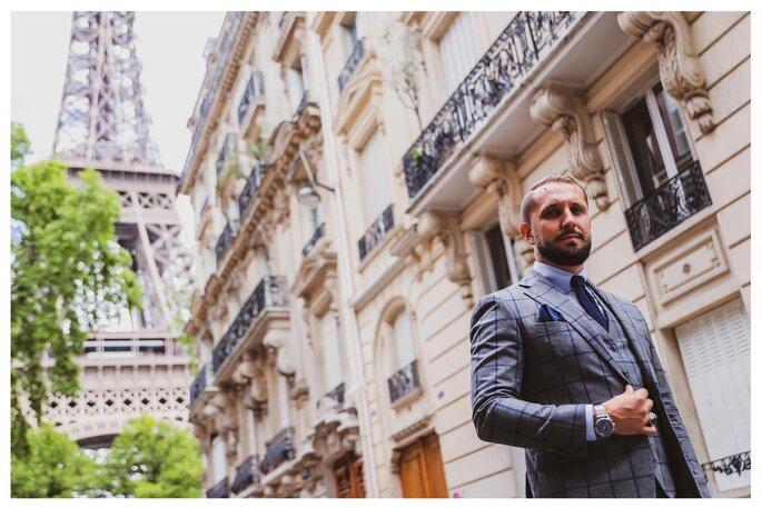 Un homme élégant en costume gris à carreaux, la Tour Eiffel en toile de fond