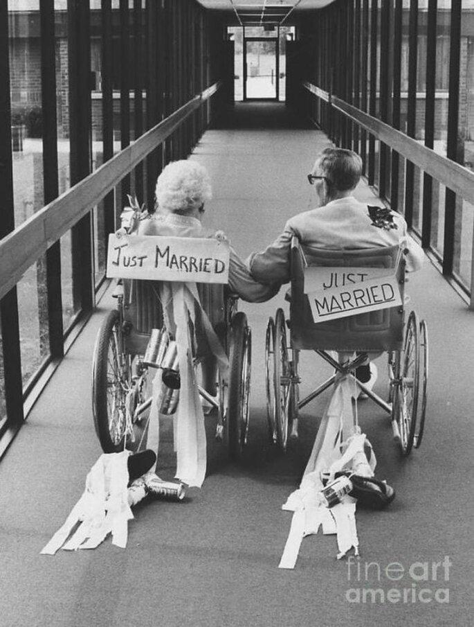 casal de idosos em cadeira de rodas com placa just married