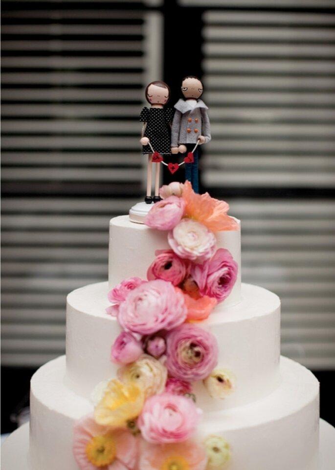 Pastel de boda blanco, a 3 niveles decorado con flores en cascada y una pareja de personajes