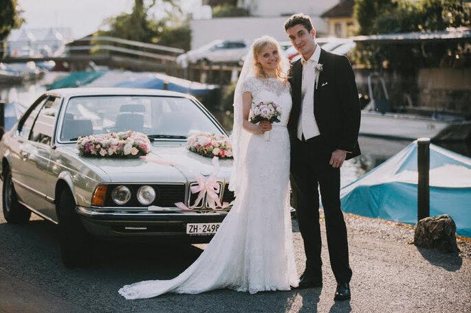 Elena & Ralf vor ihrem Hochzeitsauto nach dem Ja-Wort im Schloss Meggenhorn. Elena trägt ein bodenlanges Brautkleid mit Spitzeneinsätzen.