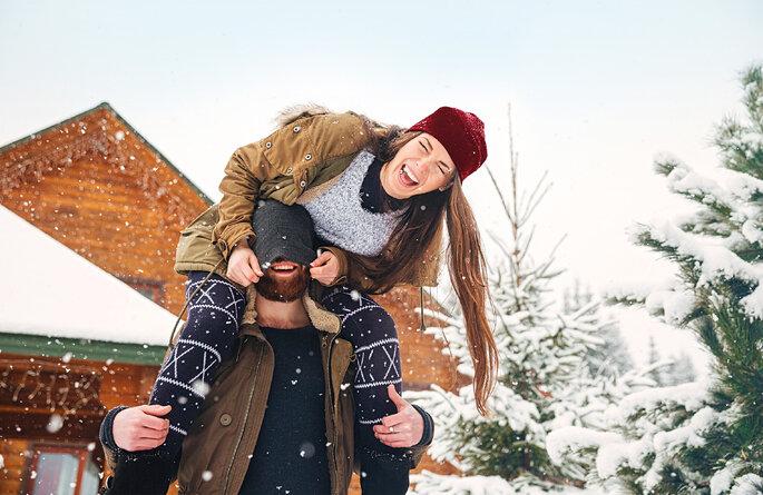 glückliches Paar lachend in Winterlandschaft