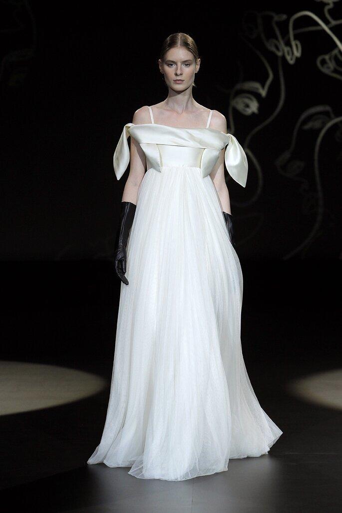 Vestido de novia para embarazada de corte imperio con falda de tul, tirantes y mangas sobrepuestas con caída hacia los hombros