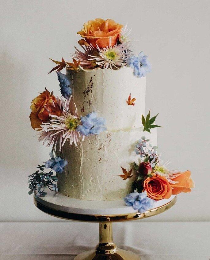 Hochzeitstorte minimal style mit Sommerblüten in blau und orange und rosa