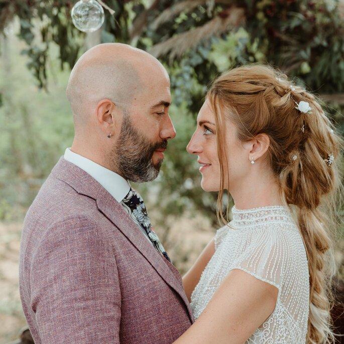 Un couple de mariés enlacés se regarde tendrement dans les yeux. Tenue du marié originale.