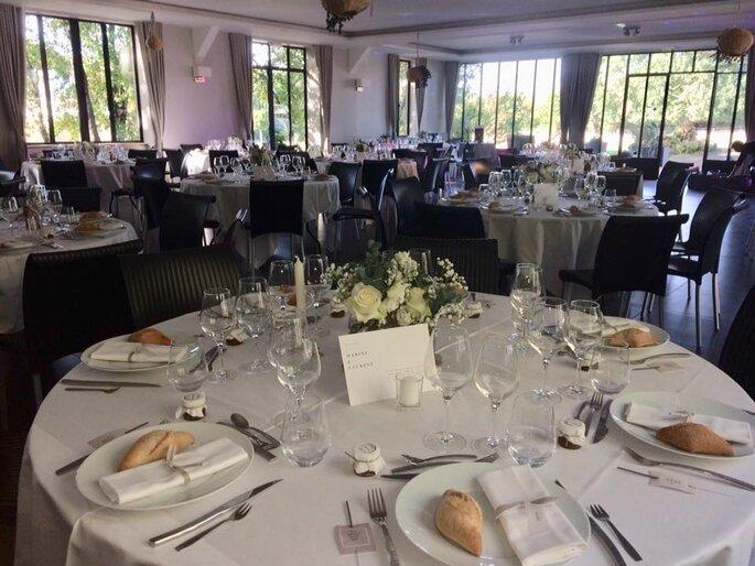 Plusieurs tables décorées pour un mariage, à l'intérieur d'un lieu de réception