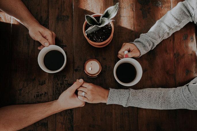 casal a beber café de mãos dadas