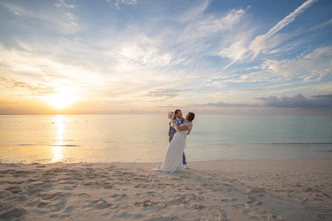 Un couple de mariés s'enlace sur une plage au bord de l'eau, au coucher du soleil.