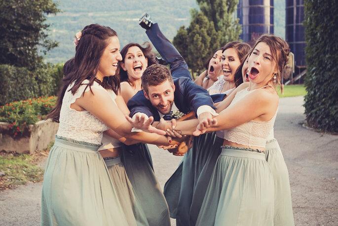 Hochzeitsfoto. Bräutigam wird von weiblichen Gästen in die Luft geworfen