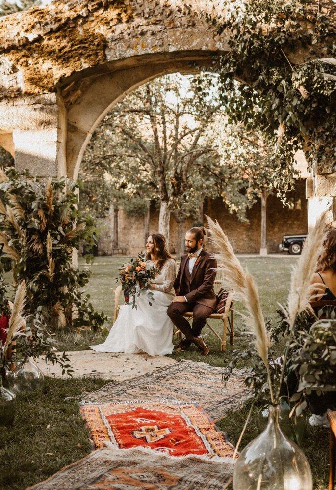 Une cérémonie civile se tient sous un porche de pierres anciennes, orné d'une décoration végétale dense.