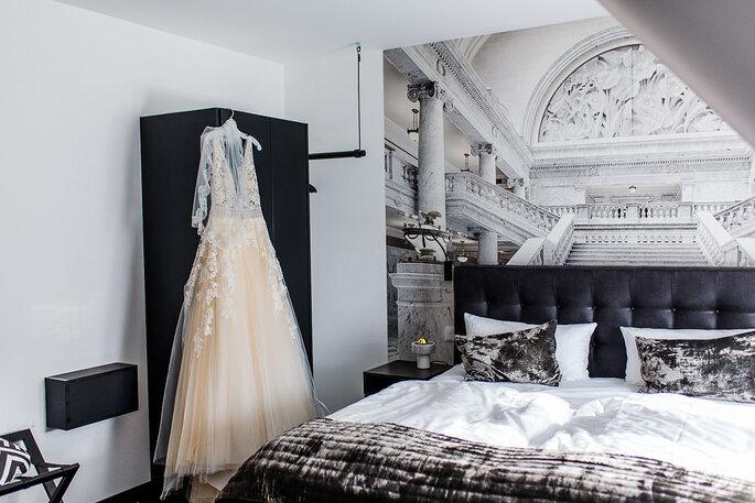 Das edle Spitzenkleid von Enzoani hängt im Hotelzimmer am Schrank.