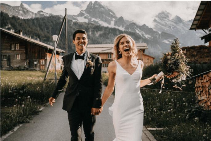 Paar rennt strahlend in die kamera mit bergen im hintergrund