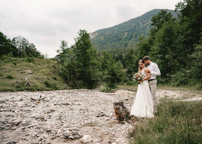 Brautpaar steht verliebt in Natur vor Berglandschaft.