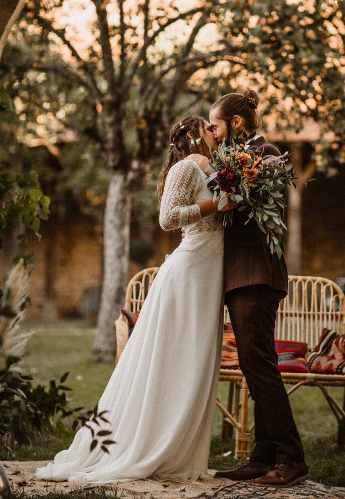 Un couple de marié s'embrasse, au premier plan le bouquet de la marié végétal aux tons terracotta