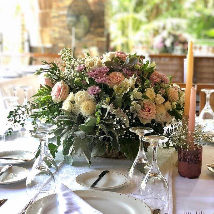 Decoración con flores para las mesas y velas rosa y amarilla