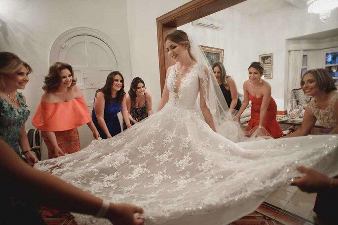 Novia colocándose su vestido y ayudada por sus damas de honor