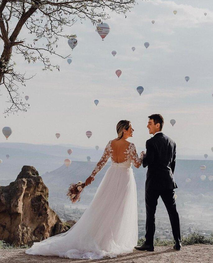 Casal de noivos em montanha, com balões ao fundo.