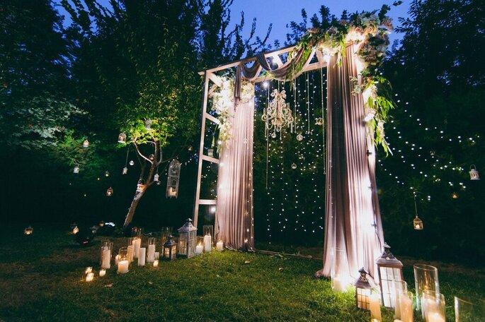 Une arche décorée et des bougies allumées pour une cérémonie laïque nocturne