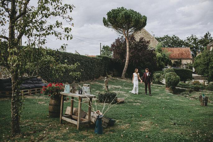 Un couple de mariés main dans la main dans un parc joliment entretenu avec des bâtisses au cachet historique en toile de fond