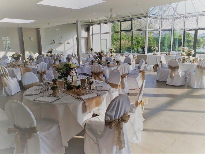 Une salle de réception de mariage baignée de lumière naturelle et décorée dans des tons très nature
