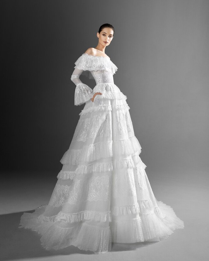 Zuhair Murad vestido de novia en corte princesa de mangas largas con volantes de encaje en los hombros, mangas, y falda, con hombros caídos, escote recto y decorado con encajes y transparencias.