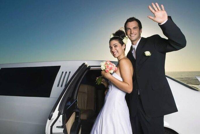 Un couple de mariés entrant de leur voiture de luxe après leur cérémonie